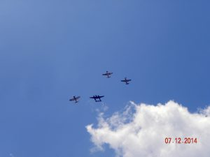Reverse 'Missing Man' formation with Corsair and 2 Mustangs breaking off from formation with P-38 Lightning