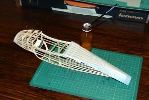 I begin by gluing paper to the bottom of the fuselage. Comienzo pegando el papel de la parte de abajo del fuselaje.