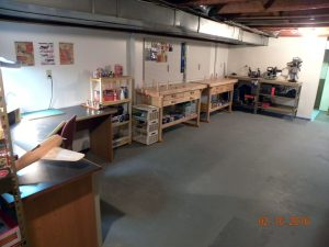 Completed walls with new bench top height electrical outlets, pegboard, and work benches and storage shelves.